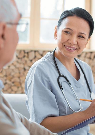 Friendly nurse speaking with senior man