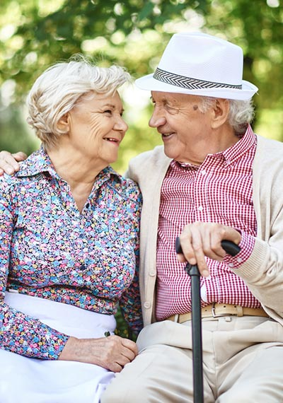 Senior couple smiling at each other on a bench in the park