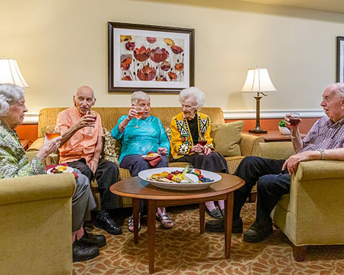 Group of 5 seniors sitting on couch and chairs with drinks and food tray on table in front of them