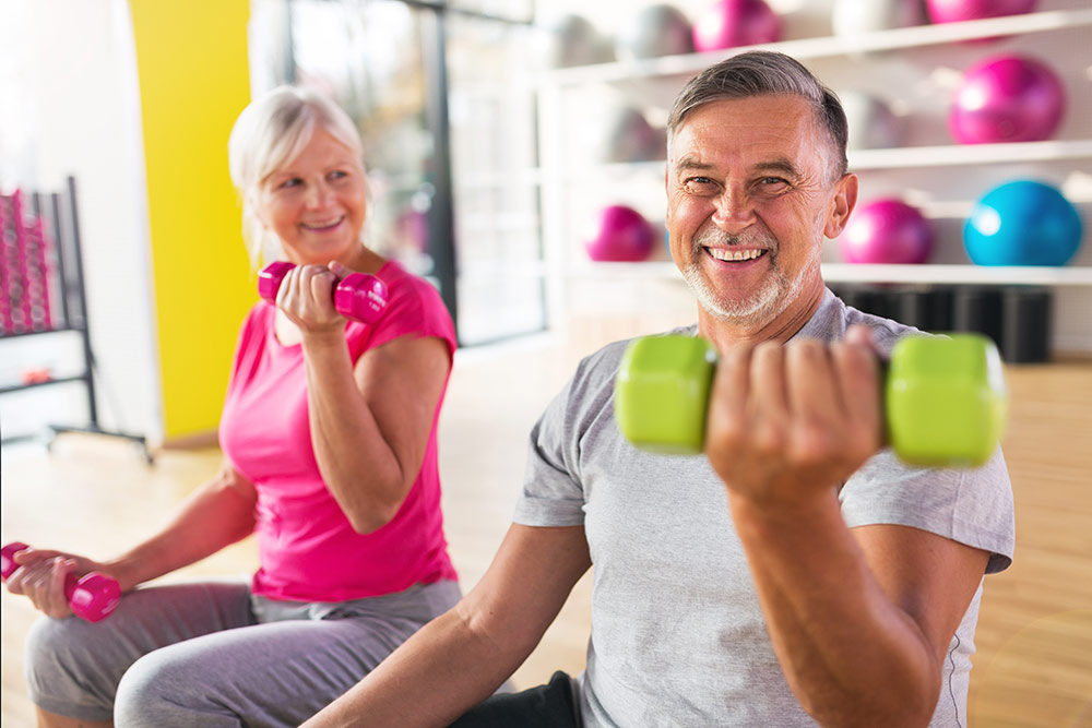 Senior couple working out, exercising, lifting free weights