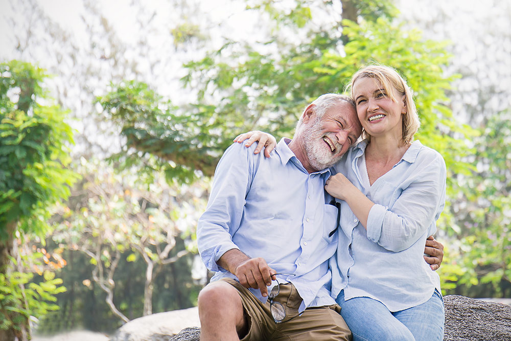 Happy senior couple sitting on a rock outside smiling