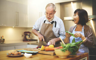 Senior couple making a healthy meal with veggies in kitchen