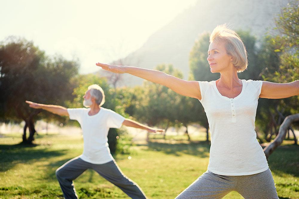 Senior man and woman doing yoga outside