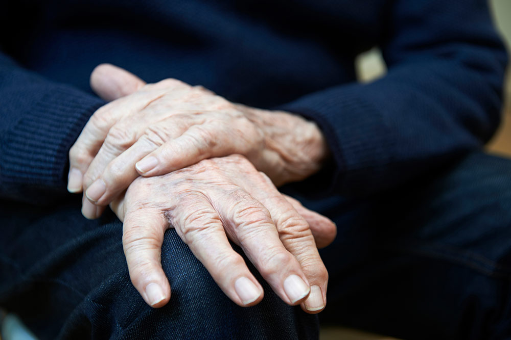 Close up of senior hands with tremors, parkinsons