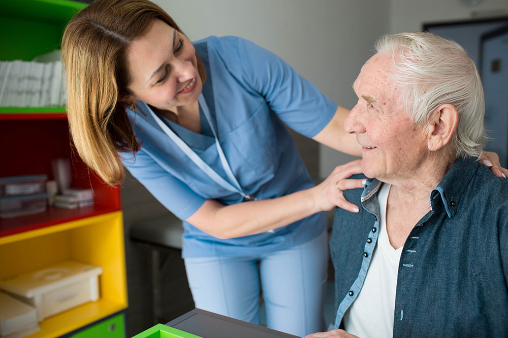 Senior man with caregiver in assisted living community