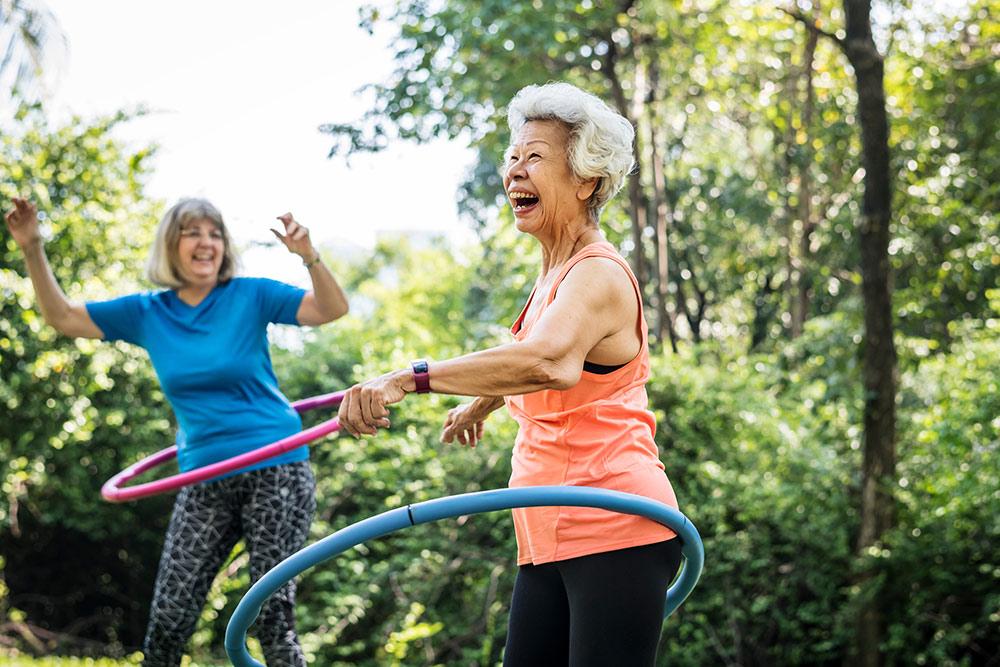 Senior women having fun exercising outside in senior living community