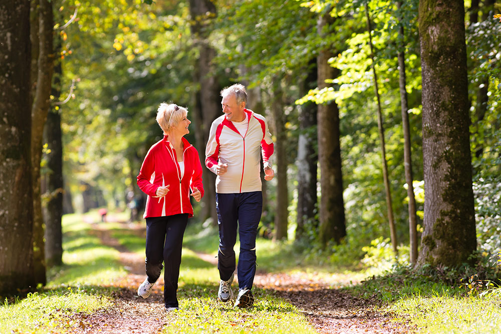 Senior couple happy and jogging outside in nice weather in senior living community in Rancho Mirage