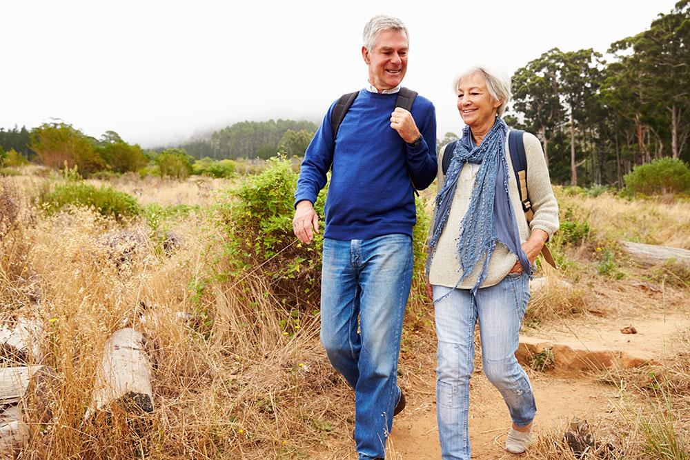 Happy senior couple walking outside smiling