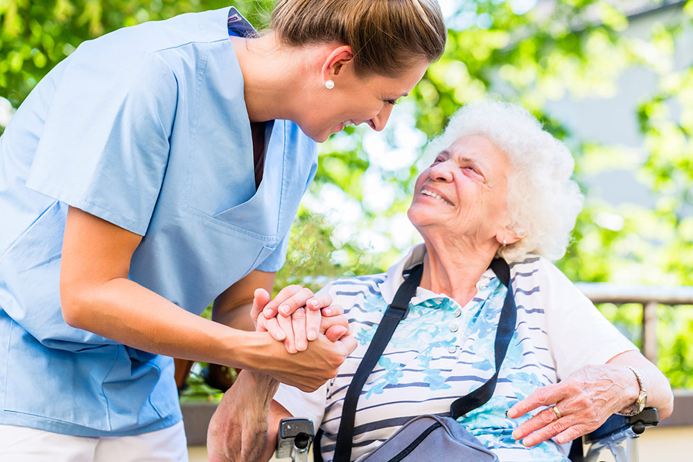 Senior woman smiling and looking up at caregiver in senior living community