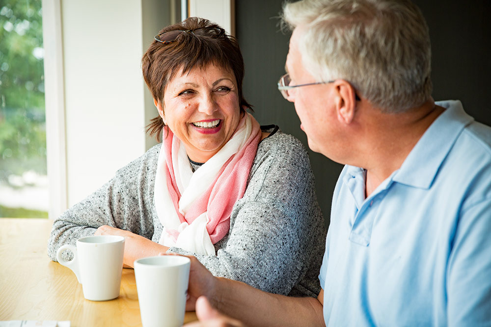 Seniors talking and smiling while sitting and drinking coffee