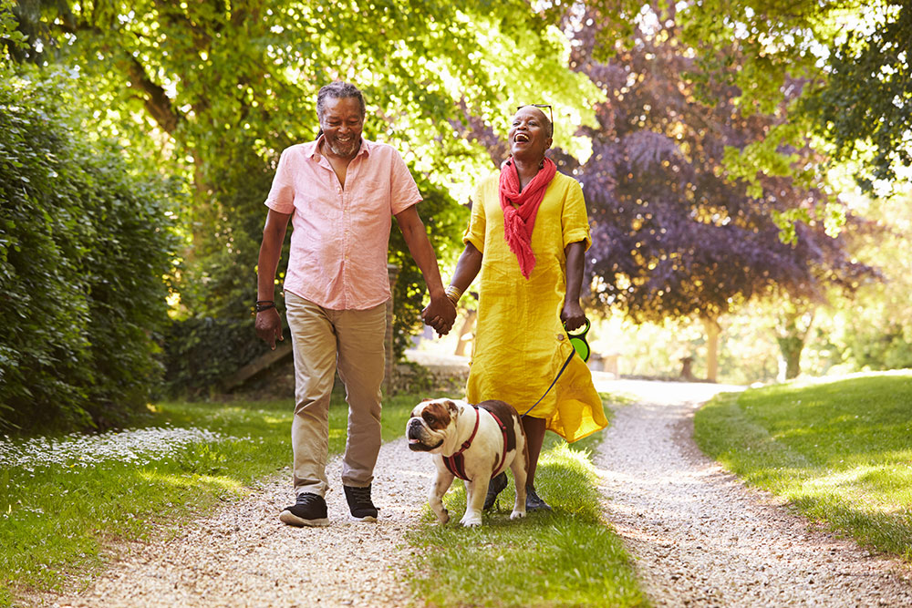 Senior couple walking outside with dog, laughing and smiling