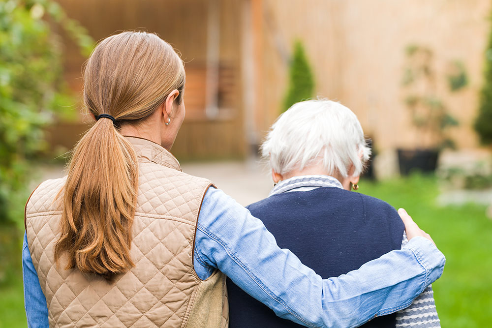 Caregiver walking with senior family member to new home in memory care assisted living