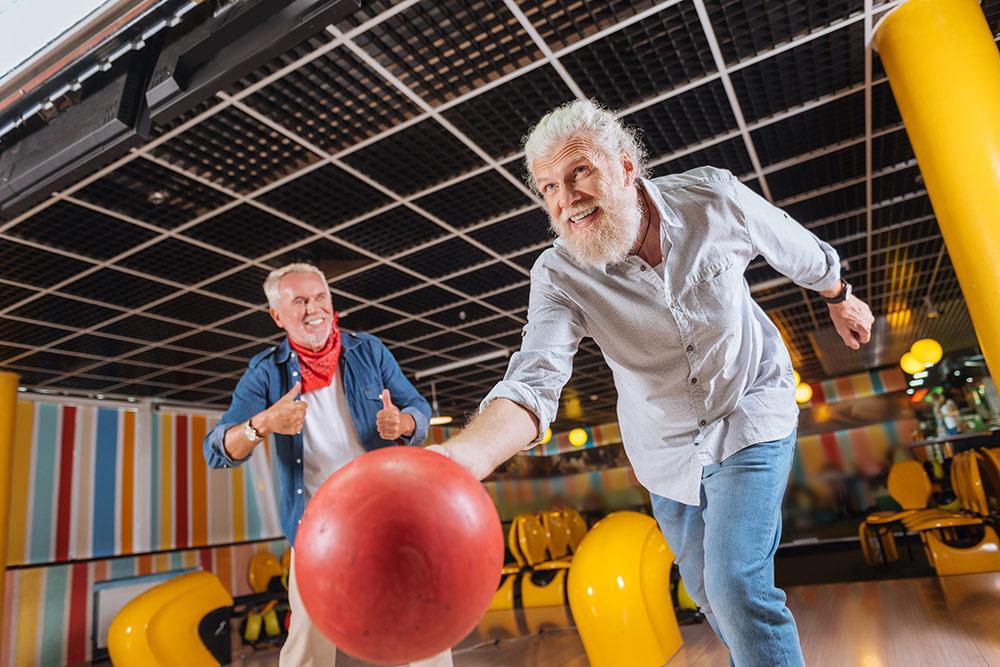 Two senior men having fun bowling