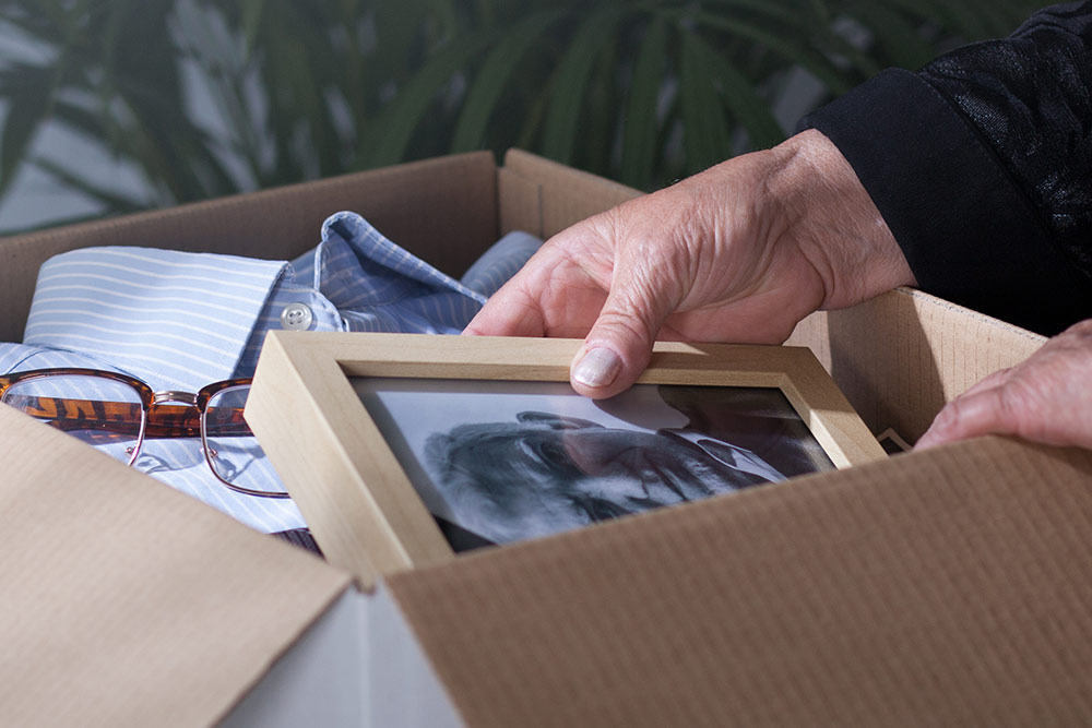 Close up of box with belongings and senior hands holding photo