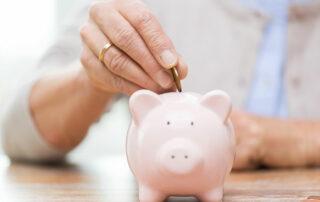 Close up of senior putting money in piggy bank, saving money for retirement