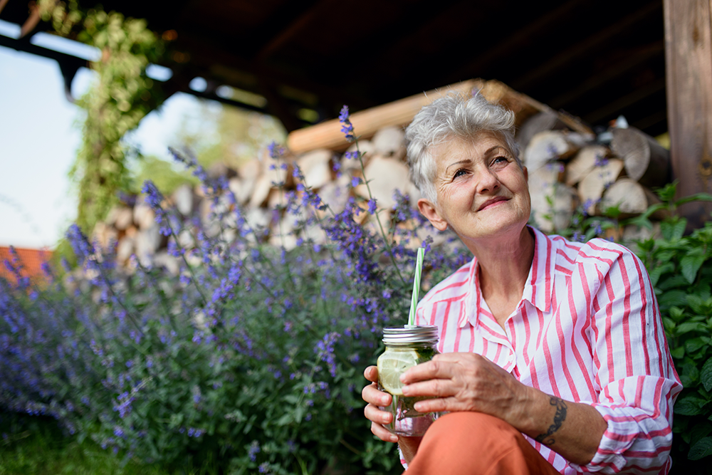 Senior woman sitting outside drinking a glass of water