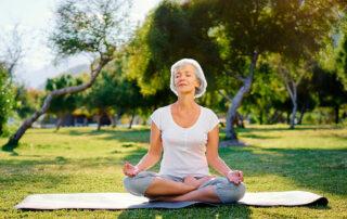 Senior woman meditating outside in park