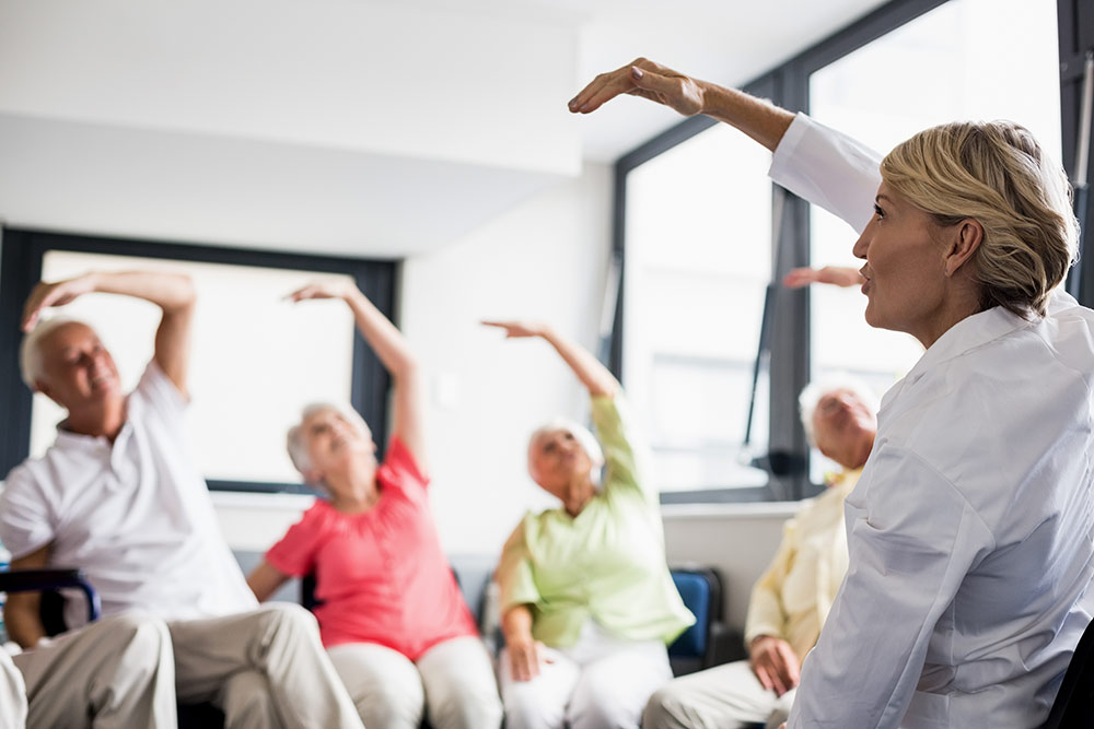 Seniors doing chair exercises with instructor in senior assisted living