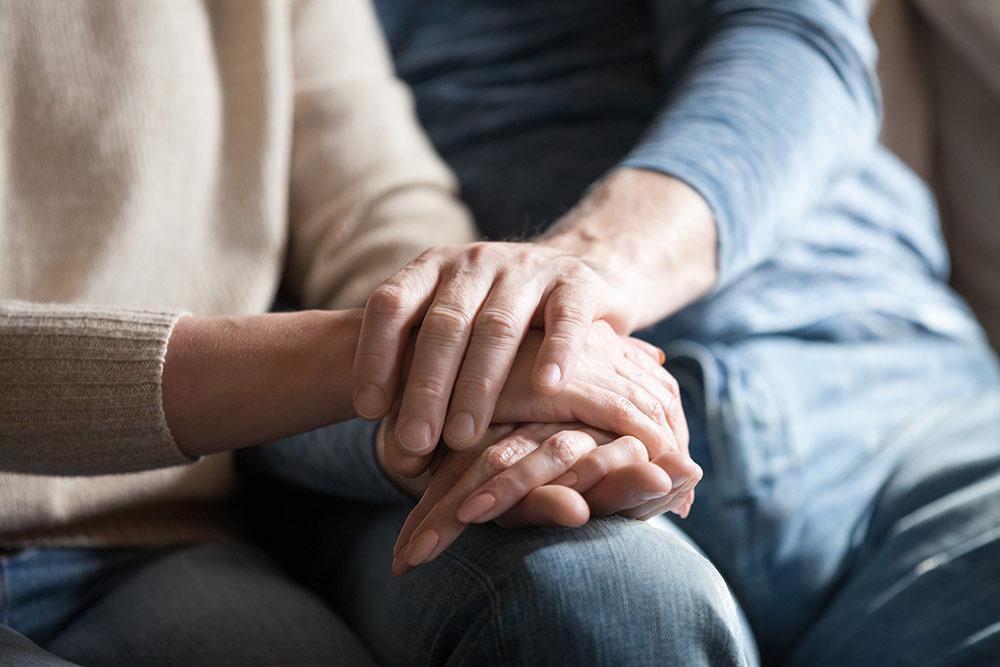 Senior hands holding caregiver hands
