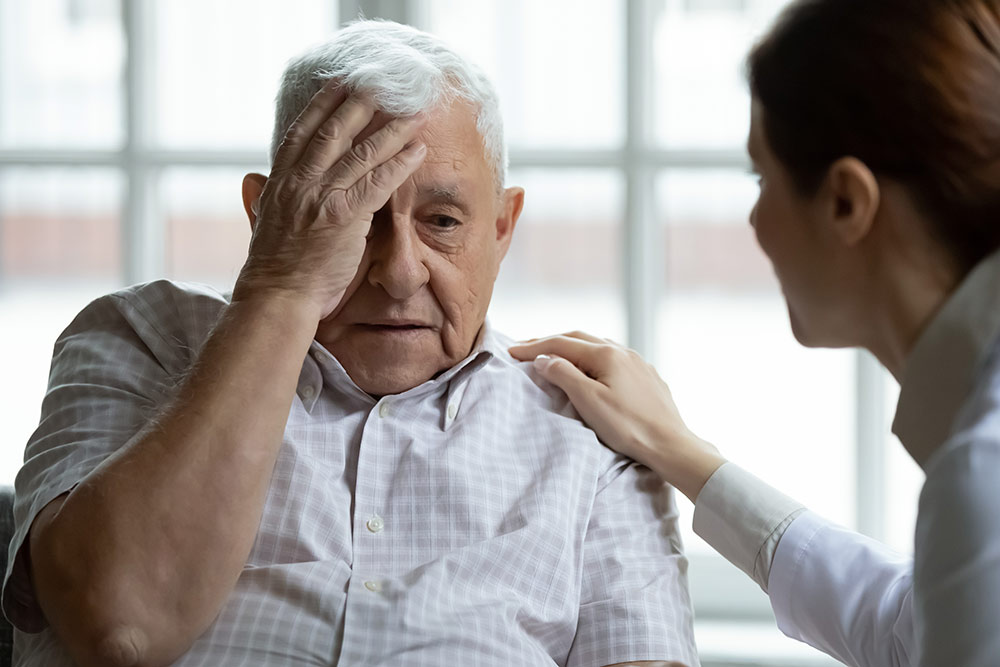 Senior man with dementia holding head, forgetful, memory loss, with caregiver