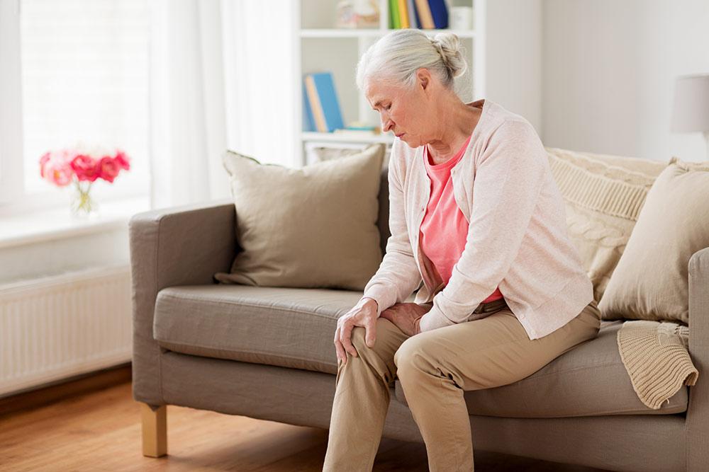 Senior woman sitting on couch holding knee, knee pain, arthritis