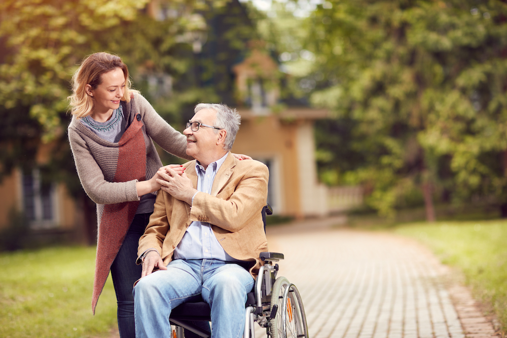 Senior man in a wheelchair and his caregiver out for a walk.